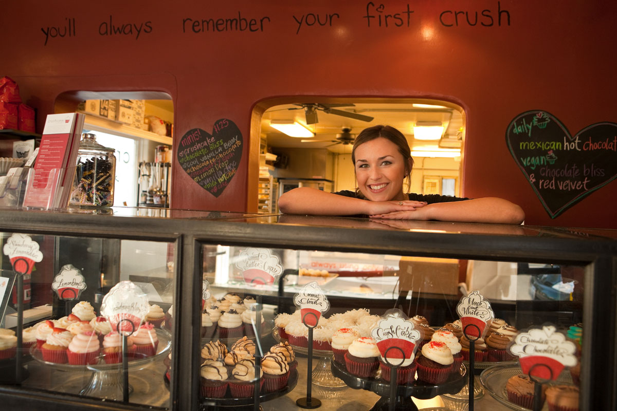 portrait of young woman behind counter of cupcakes