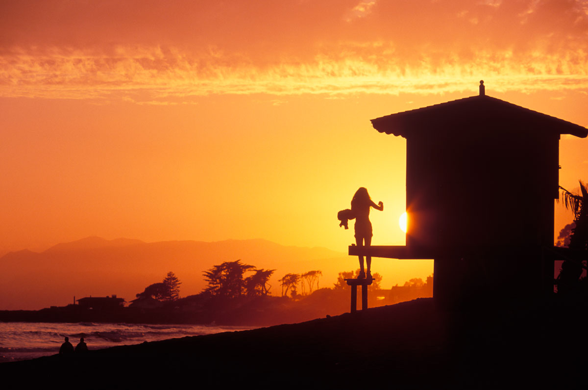 Woman on lifeguard tower at sunset