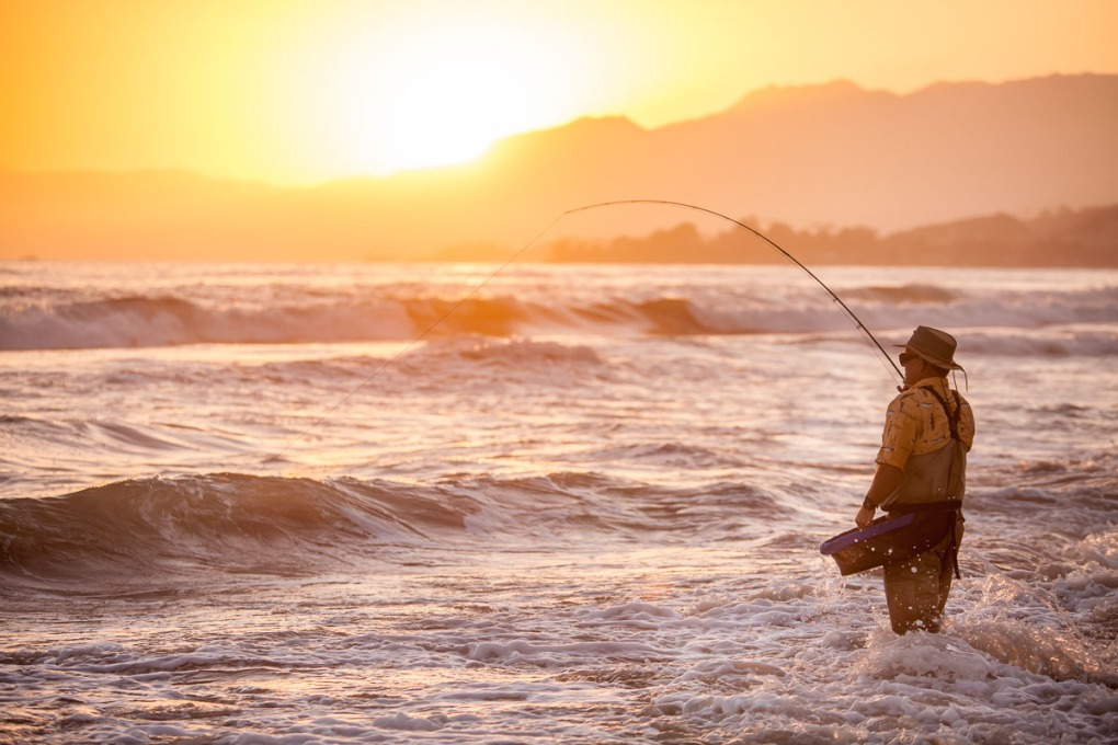 Fisherman on beach at sunset