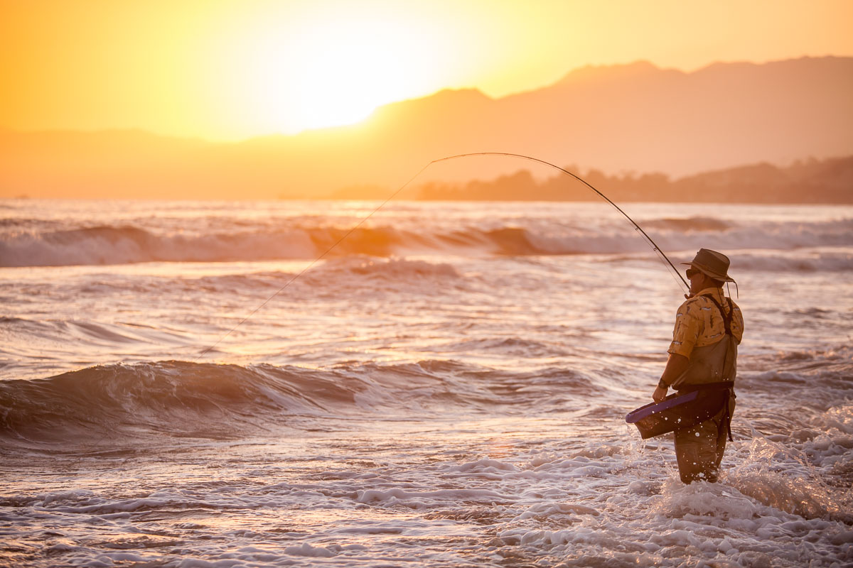 Fisherman on beach at sunset