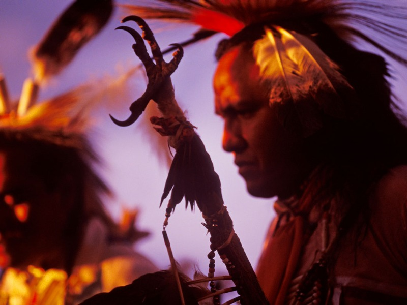 Traditional Native American dancers sidelit by the setting sun