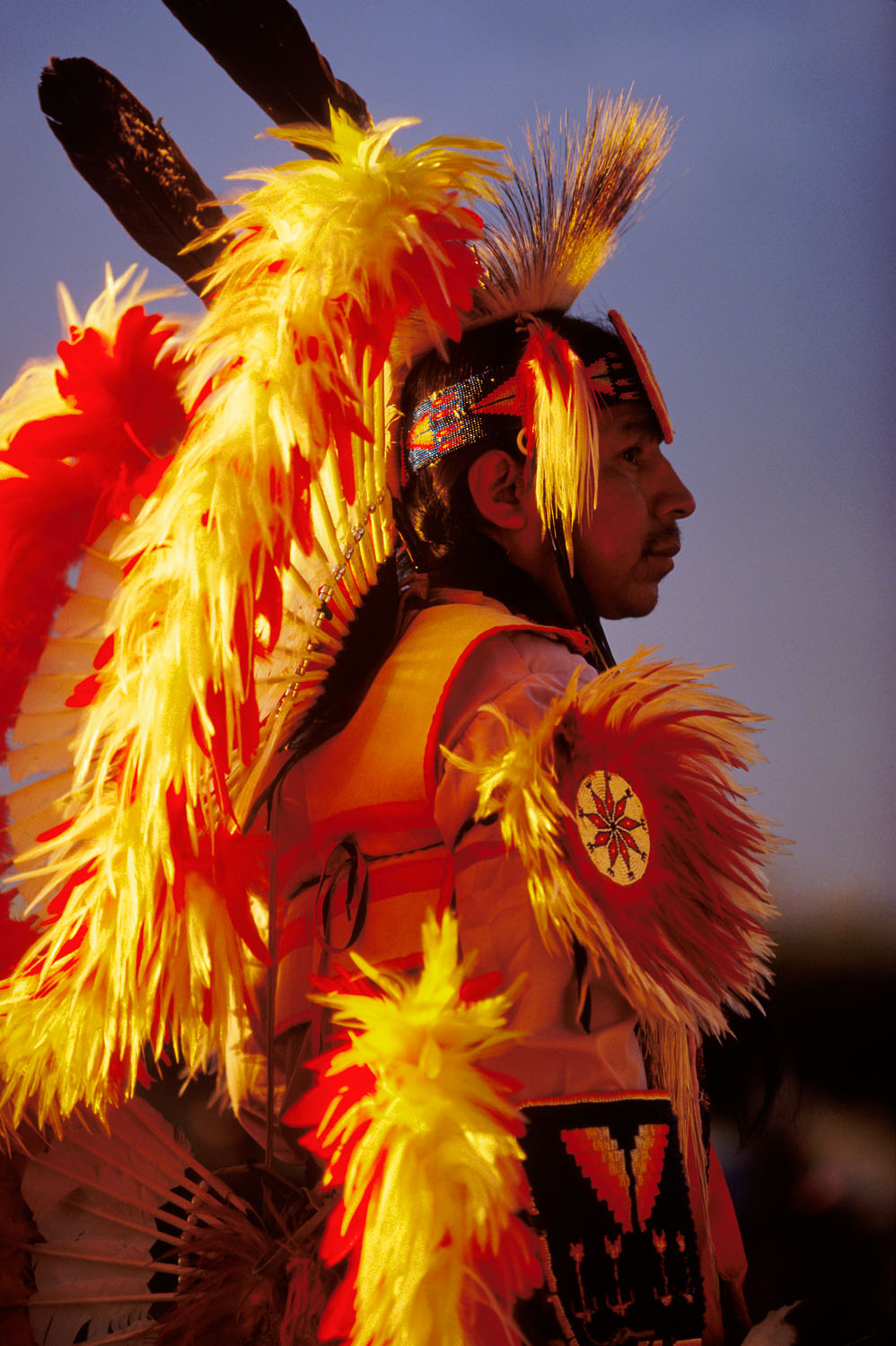 Native American Fancy Dancers sidelit by the setting sun at Magic Hour