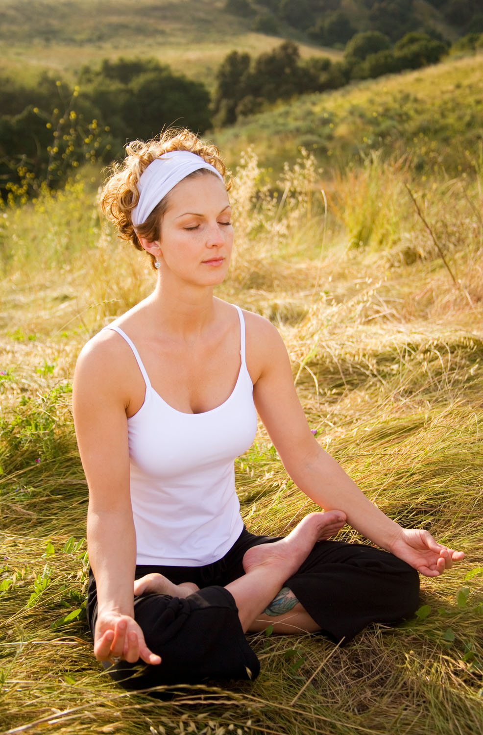 Woman practicing yoga is backlit by the setting sun at Magic Hour