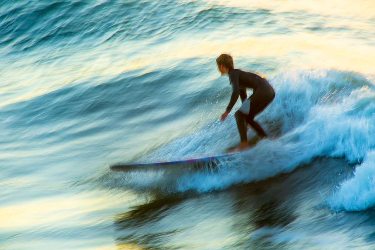 Slow panning image of a surfer at sunrise
