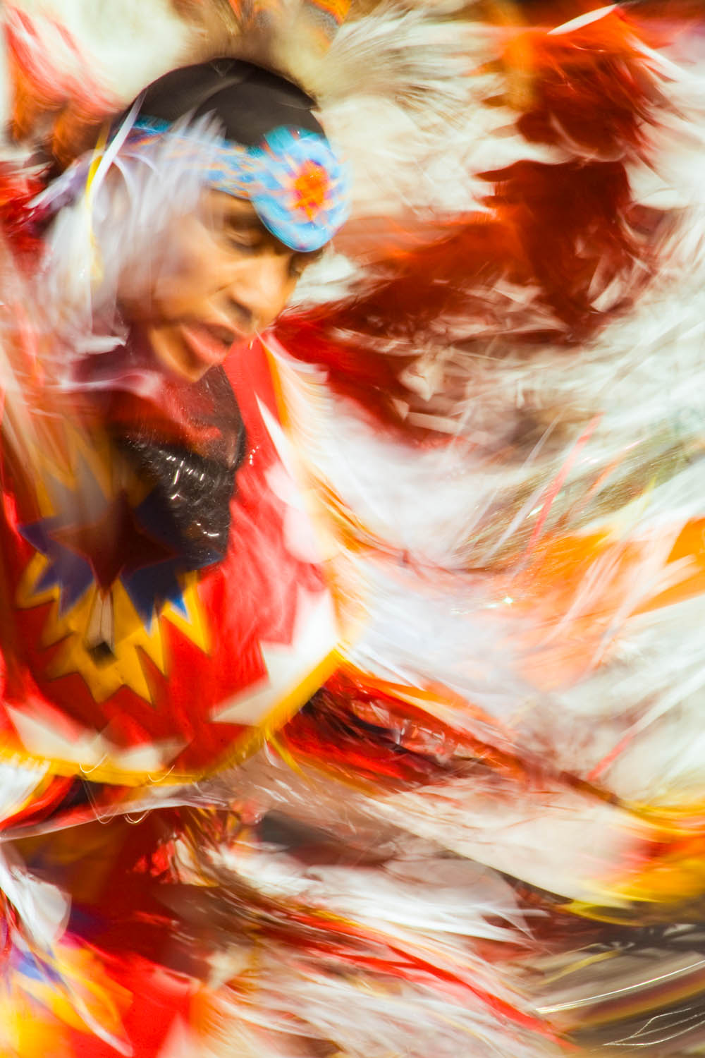 Motion blurs the regalia of a spinning Native American dancer while leaving a somewhat sharp face