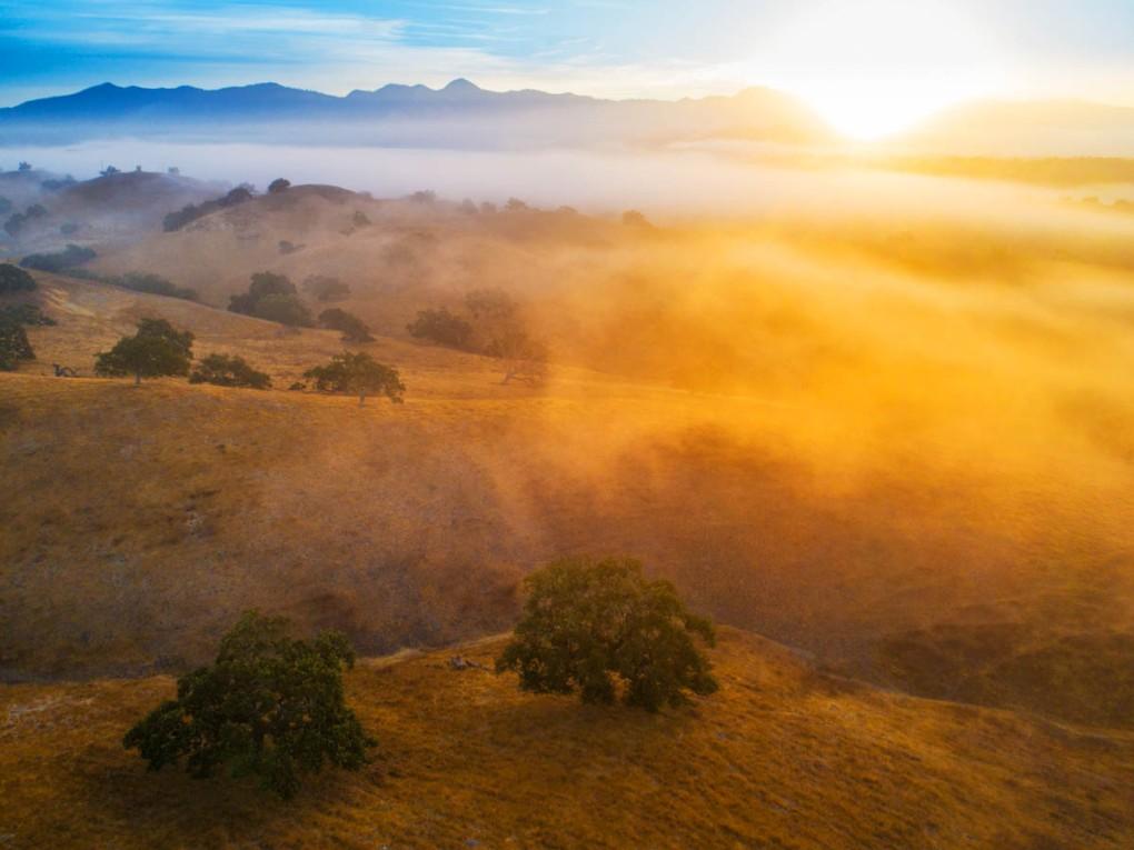 The sun peaks over a mountain ridge at sunrise, backlighting the morning fog