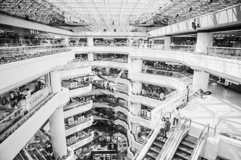 Black and white photograph of a modern shopping mall